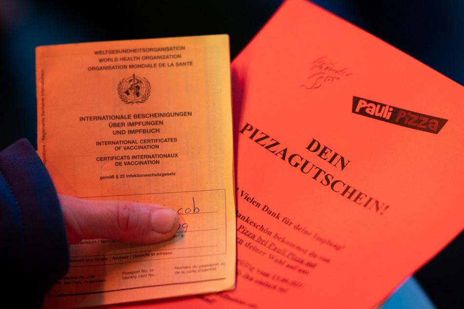 13.09.2021, Hamburg: Eine Frau hält ihren Impfpass und einen Pizza-Gutschein nach ihrer Impfung gegen das Coronavirus im Rahmen der Aktion «Kiez-Piks» in der Bar «Wunderbar» nahe der Reeperbahn im Stadtteil St. Pauli. Foto: +++ dpa-Bildfunk +++
