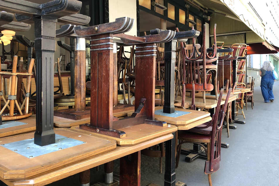 Tische und Stühle stehen gestapelt vor einem Bistro im 14. Pariser Stadtbezirk. Von Dienstag an dürfen Lokale in Frankreich wieder Gäste empfangen, müssen aber Sicherheitsbestimmungen einhalten.