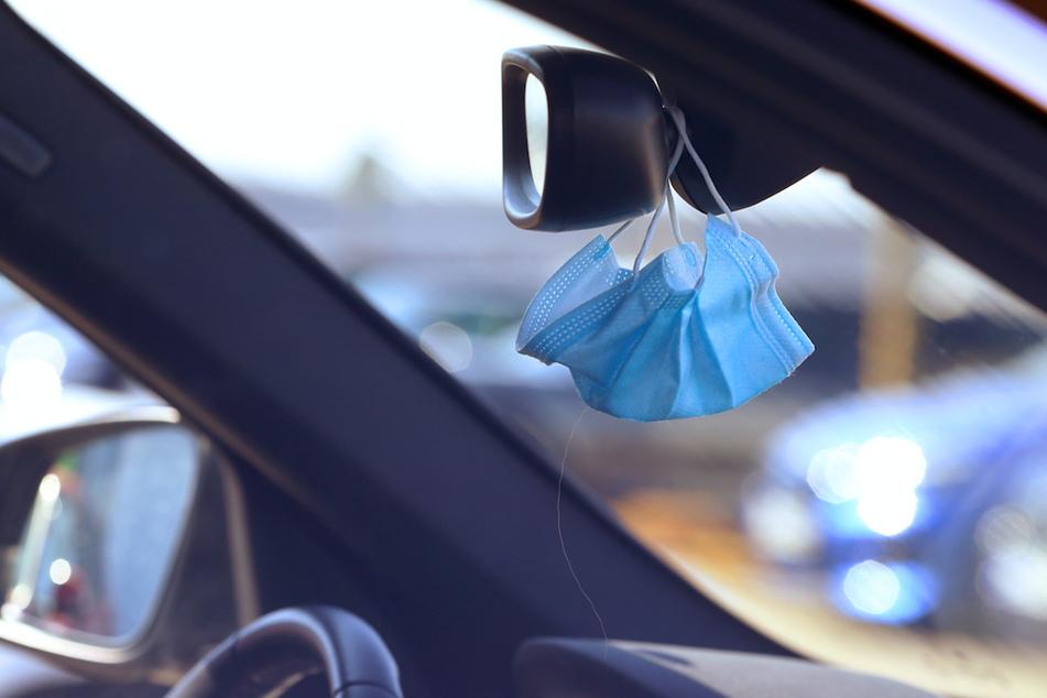 Ein medizinischer Mundschutz hängt am Rückspiegel eines Autos.