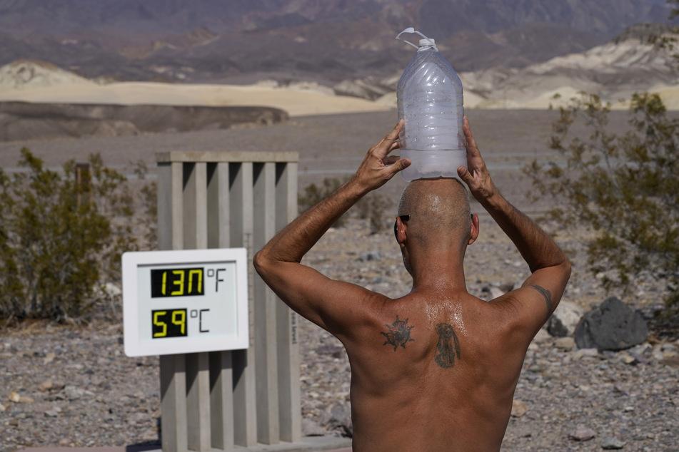"""Bei einer Temperatur von 59 Grad kühlt sich ein Mann im """"Death Valley""""-Nationalpark in den USA mit einer mit Eiswasser gefüllten Plastikflasche auf dem Kopf ab."""
