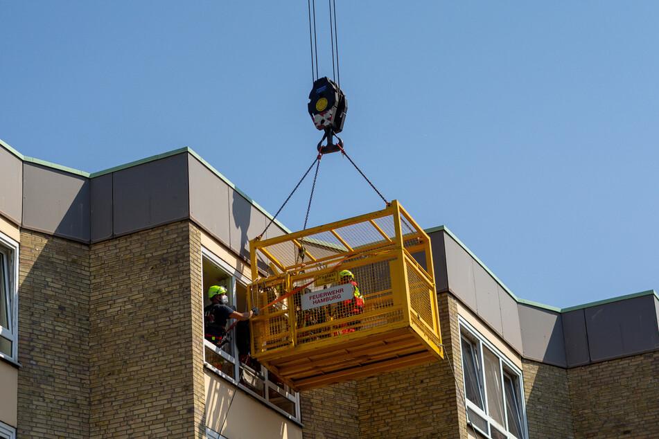 Mit Hilfe eines Krans wird der Mann aus seiner Wohnung transportiert.