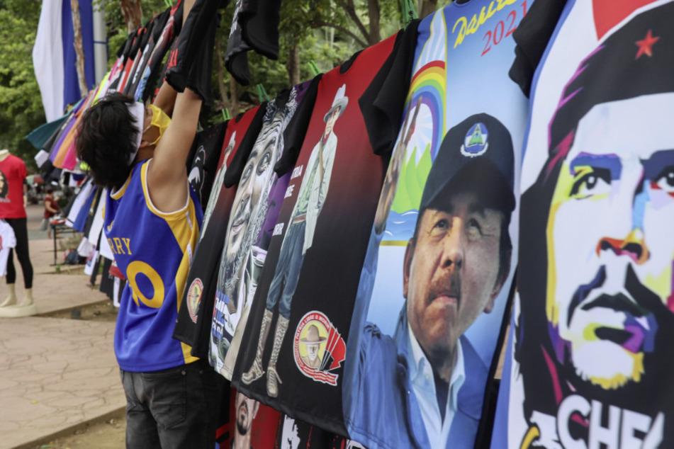 Ein Mann mit Mundschutz verkauft T-Shirts mit Abbildungen des nicaraguanischen Präsidenten Daniel Ortega oder des Revolutionsführers Che Guevara.