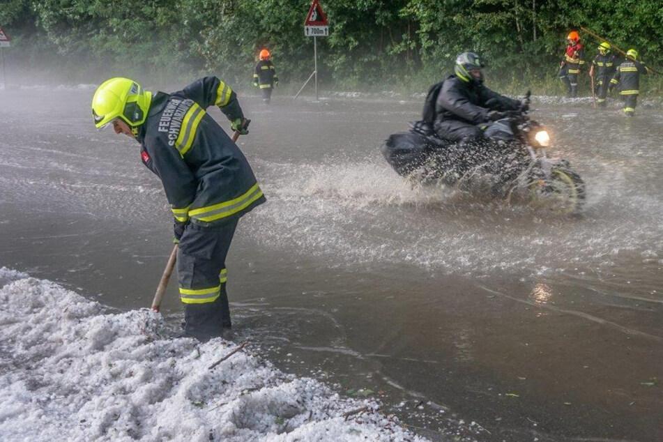 Einsatzkräfte der Feuerwehr müssen nach einem Unwetter Hagelkörner beiseite schieben.