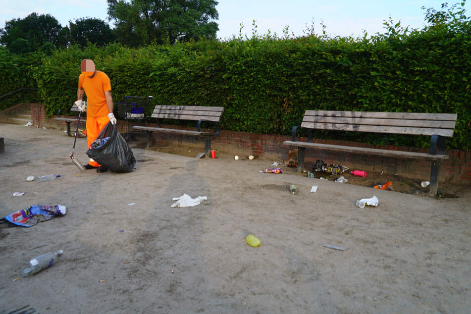 Ein Mitarbeiter der Stadtreinigung sammelt Müll im Stadtpark auf.
