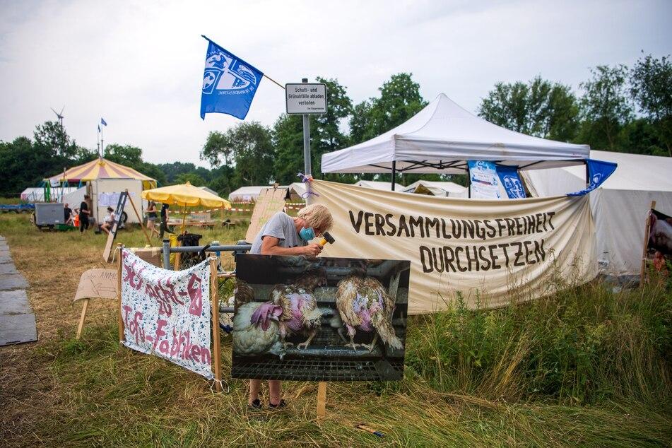 """Plakate werden vor dem Protestcamp vom Bündnis """"Gemeinsam gegen die Tierindustrie"""" aufgehängt."""