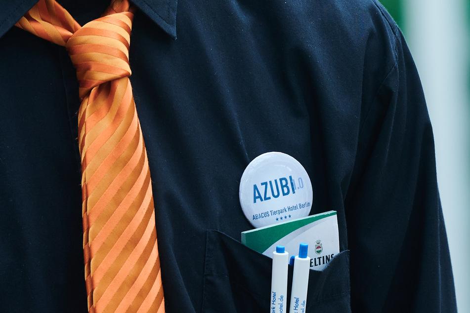 """""""AZUBI"""" steht auf dem Button eines Auszubildenden im Hotelfach im Restaurant des Abacus Tierpark Hotels."""