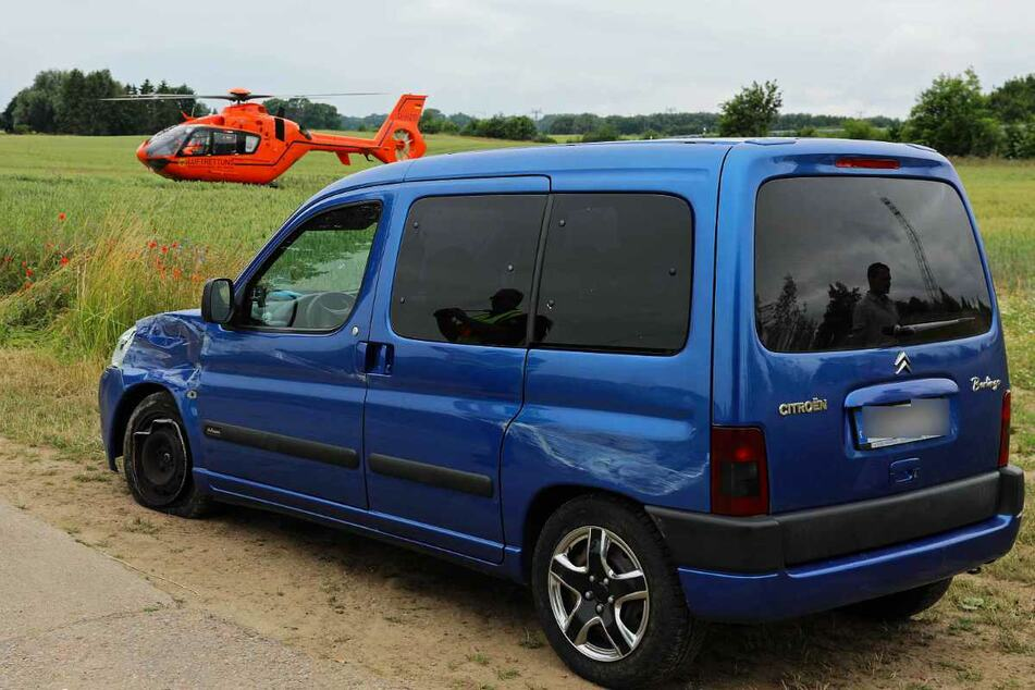 Die Spuren des Unfalls sind am Citroën deutlich zu erkennen. Im Hintergrund steht der Rettungshubschrauber auf einem Feld.