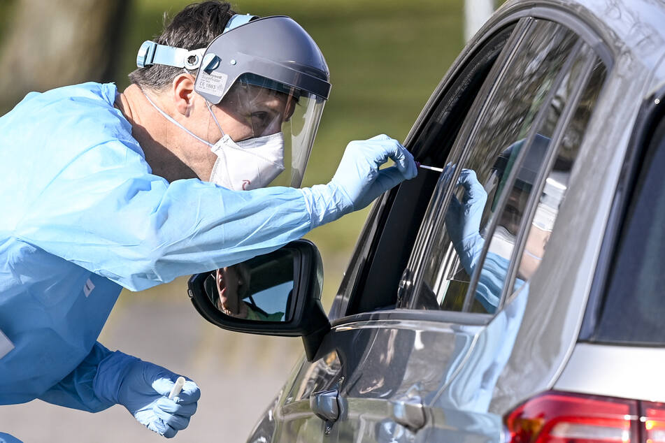 Ein Arzt führt bei einer Autofahrerin einen Covid-19-Test durch.