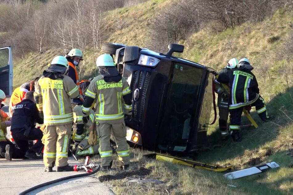 Polizei, Feuerwehr und Rettungsdienst stehen um den Ford und kümmern sich um verletzte Personen.