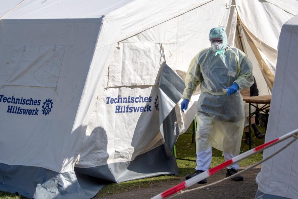 Ein Klinik-Mitarbeiter geht im Schutzanzug durch eine provisorische Ambulanz. (Symbolbild)