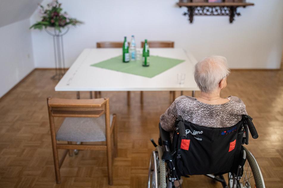 Eine ältere Frau sitzt in einem Pflegeheim in ihrem Rollstuhl vor einem Tisch.