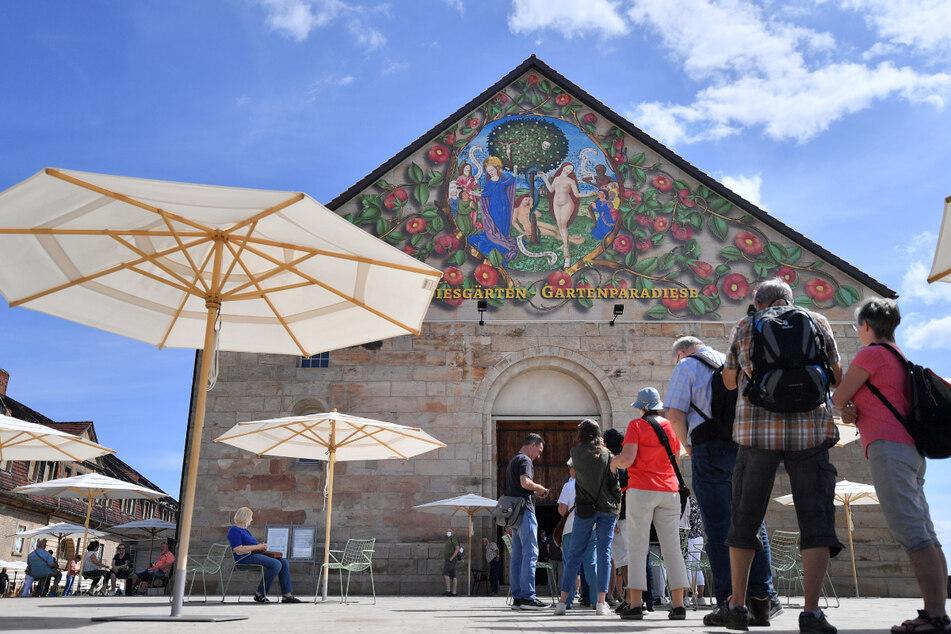 Besucher stehen am Giebel der Peterskirche auf dem Gelände der Bundesgartenschau auf dem Petersberg in Erfurt. Das Zwischenfazit nach den ersten Monaten fällt positiv aus.
