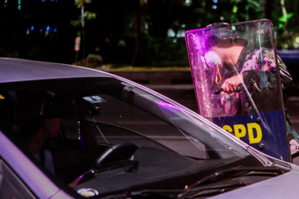 Ein Polizist mit einer Mundschutzmaske und einem Schutzschild hält an einem Kontrollpunkt einen Autofahrer an.