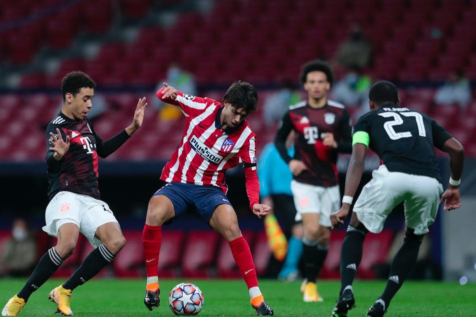 Joao Felix (M.) von Atletico Madrid kämpft mit Jamal Musiala (l.) vom FC Bayern um den Ball.