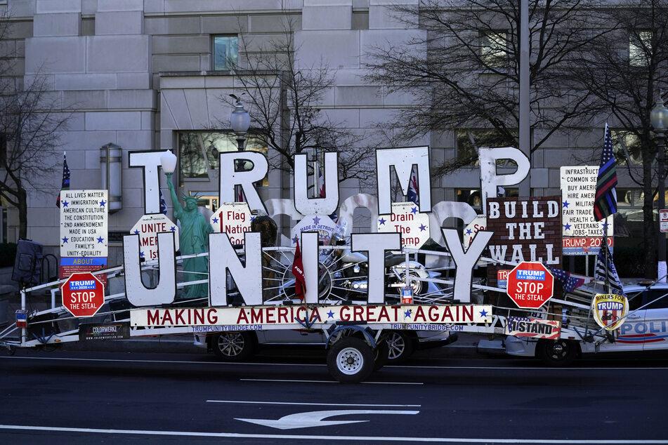 """Ein Unterstützer des scheidenden US-Präsidenten Trump ist mit einem Anhänger unterwegs, auf dem """"Trump Unity"""" (Trump-Einheit) und verschiedene Parolen wie """"Build the Wall"""" (Baut die Mauer) oder """"Making America Great Again"""" (Amerika wieder groß machen) zu lesen sind."""