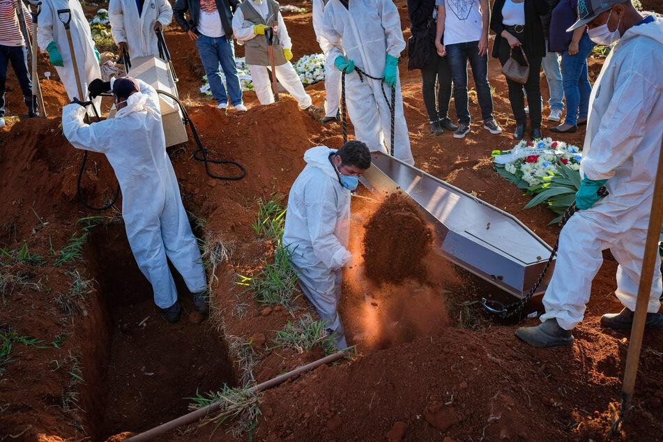 Friedhofsmitarbeiter in Schutzanzügen schaufeln Erde während einer Beerdigung auf dem Friedhof Vila Formosa inmitten der Corona-Pandemie.