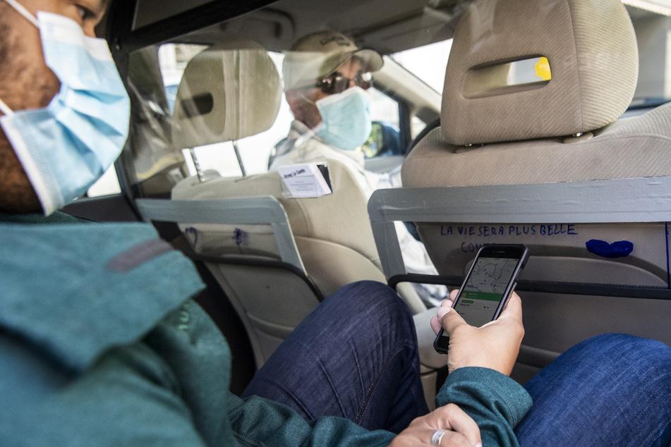 Ein Fahrer vom Fahrdienst-Vermittler Uber holt in der Schweiz einen Kunden in seinem mit einer Trennwand aus Kunststoff ausgestatteten Fahrzeug ab, beide Insassen tragen Mundschutz. (Archivbild)