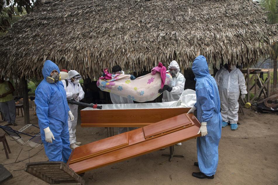 Peru, Pucallpa: Ein Regierungsteam entfernt in der indigenen Shipibo-Gemeinde von Pucallpa die Leiche einer Frau, die im Alter von 88 Jahren an den Symptomen des Coronavirus gestorben ist, aus ihrem Haus und legt sie in einen Sarg.
