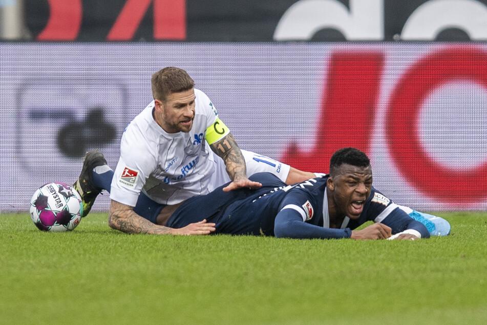Darmstadts Freistoß-Spezialist Tobias Kempe (l.) und der Bochumer Verteidiger Armel Bella-Kotchap liegen nach einem Zweikampf am Boden.