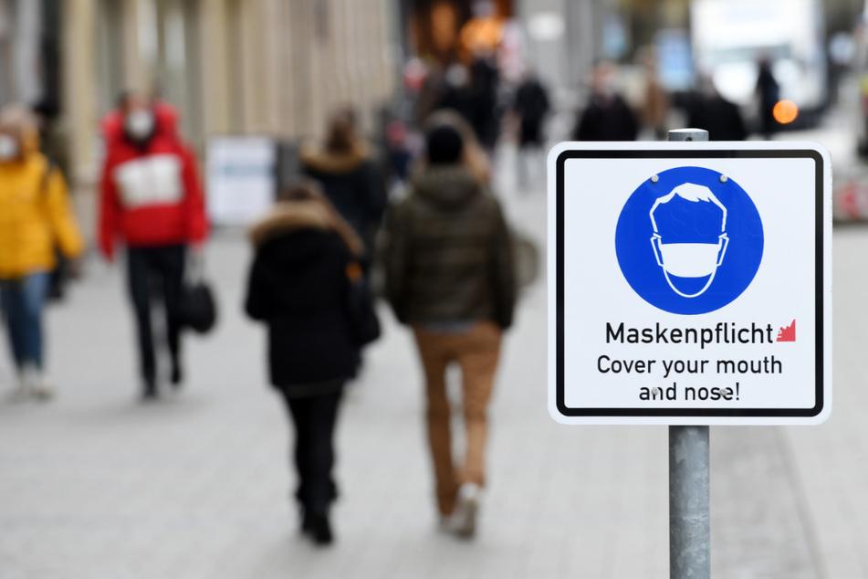 Ein Schild weist in der Münchner Innenstadt auf die Maskenpflicht innerhalb der Fußgängerzone hin.