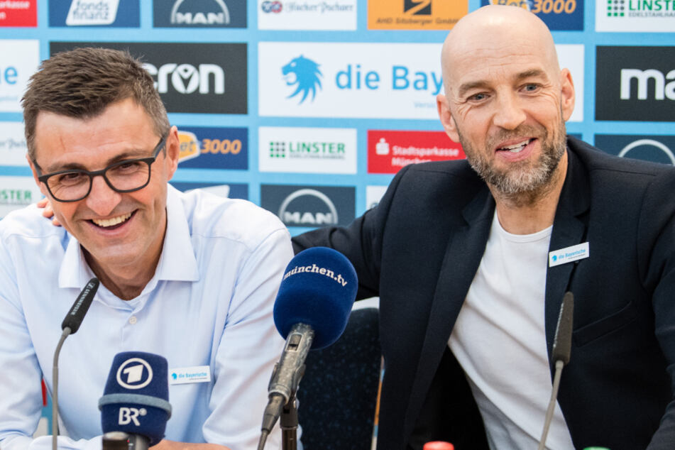 Günther Gorenzel (48, r.), Sportlicher Leiter des TSV 1860 München, legt während der Pressekonferenz den Arm um Michael Köllner (50).