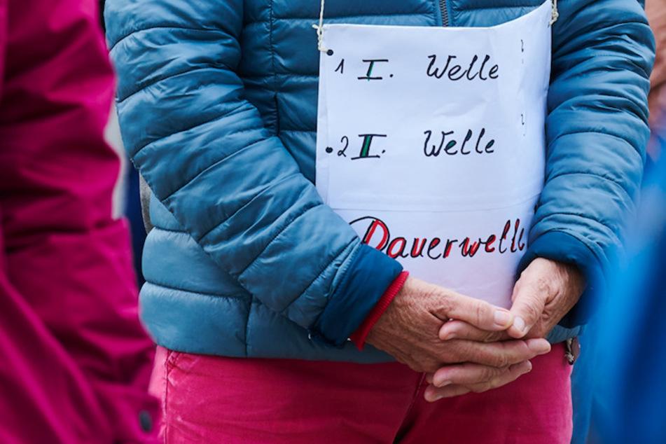 """""""1.Welle - 2.Welle - Dauerwelle"""" steht auf dem Plakat einer Demonstrantin bei einer Querdenken-Demo."""