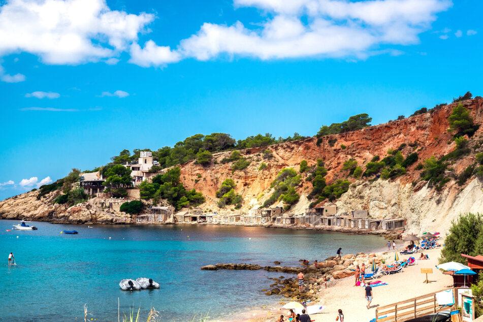 Menschen genießen die Sonne am Cala d'Hort Strand auf Ibiza.