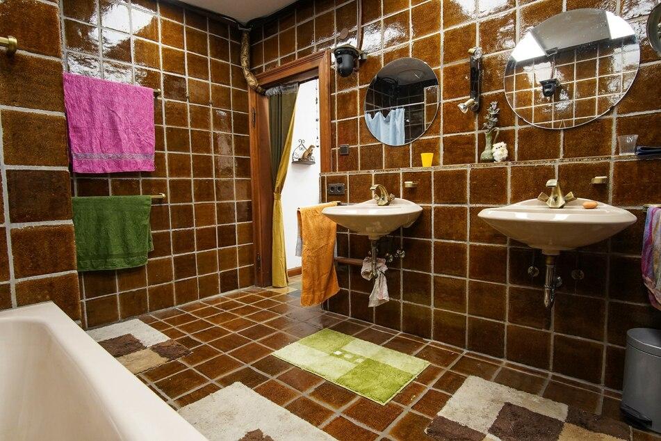 Das bescheidene Badezimmer ist mit braunen Fliesen und Waschtischen eines älteren Kalibers bestückt.
