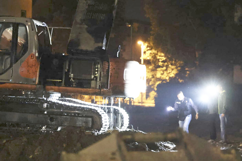 Einsatzkräfte der Polizei suchen am Tatort nach Spuren. Der betroffene Bagger war auf dem Gelände einer Baustelle abgestellt.