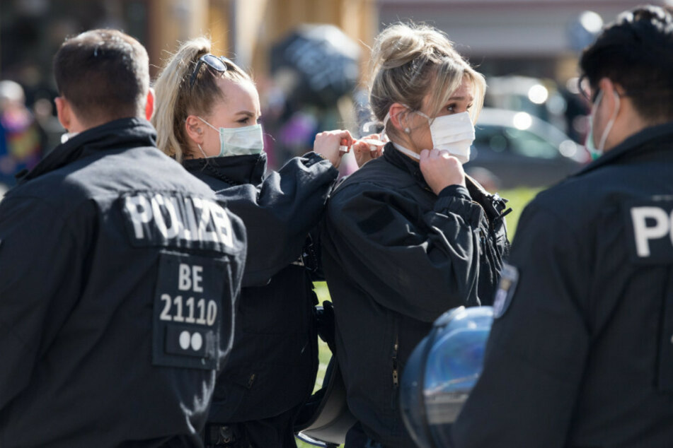 """Polizistinnen binden sich bei einer Demonstration unter dem Motto """"Grundrechte verteidigen - Sage NEIN zur Diktatur!"""" auf dem Rosa-Luxemburg-Platz gegenseitig den Mundschutz."""