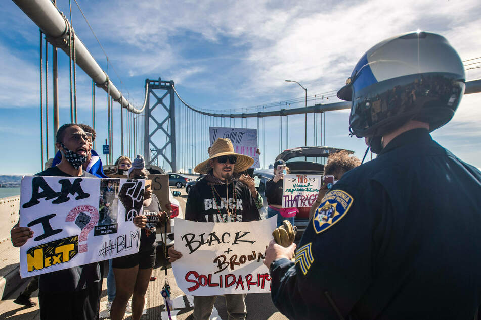 BLM protestors in front of a police officer on Bay Bridge on June 14, 2020 after the death of George Floyd.