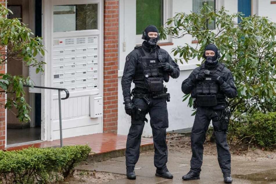 Zwei SEK-Beamte stehen während einer Razzia vor einem Hauseingang.
