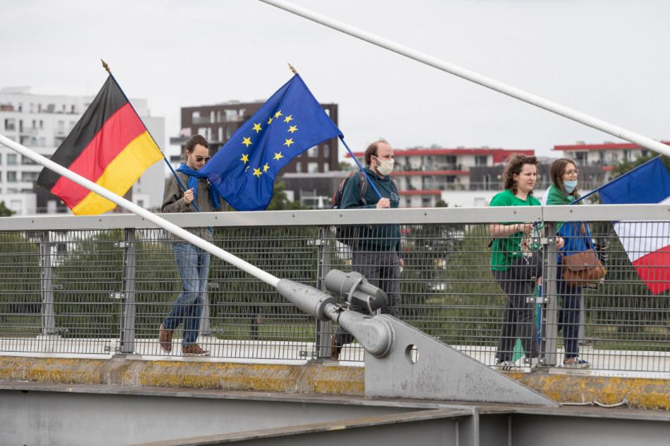 """Mitglieder pro-europäischer französischer und deutscher Verbände gehen mit der deutschen, französischen und europäischen Fahne auf der """"Passerelle des Deux-Rives"""" (Fußgängerbrücke der beiden Ufer), die das französische Straßburg mit dem deutschen Ort Kehl (Baden-Württemberg) verbindet."""