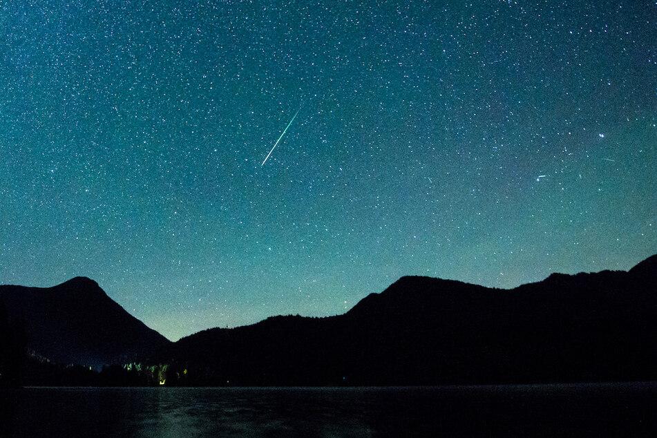 Eine Sternschnuppe leuchtet vor der Milchstraße am Himmel über dem Walchensee.