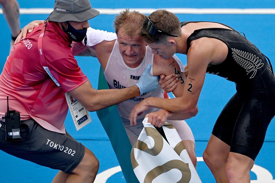 Völlig erschöpft: Kristian Blummenfelt (27, M.) musste nach seinem Olympia-Sieg gestützt und gleich in einen Rollstuhl gesetzt werden.
