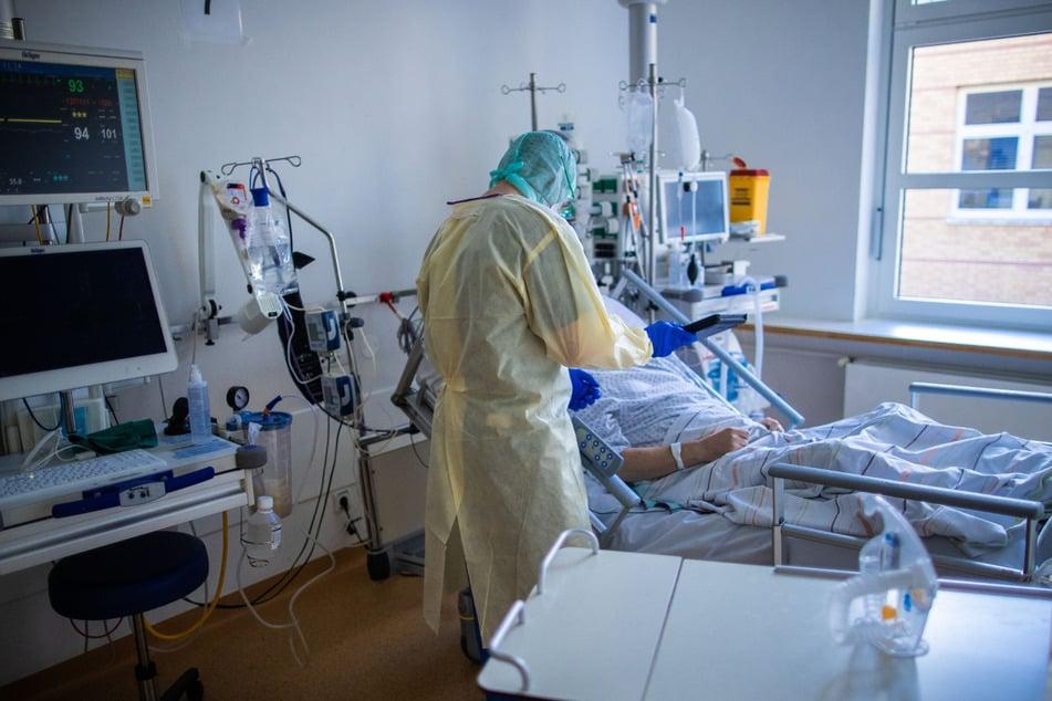 Ein Mitarbeiter behandelt im besonders geschützten Teil einer Intensivstation einen Covid-19-Patienten.