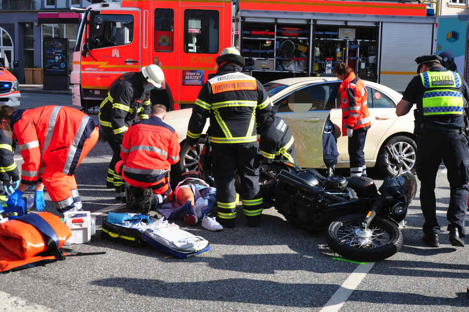 Rettungskräfte am Unfallort. Der verletzte Motorradfahrer liegt verletzt auf der Straße.
