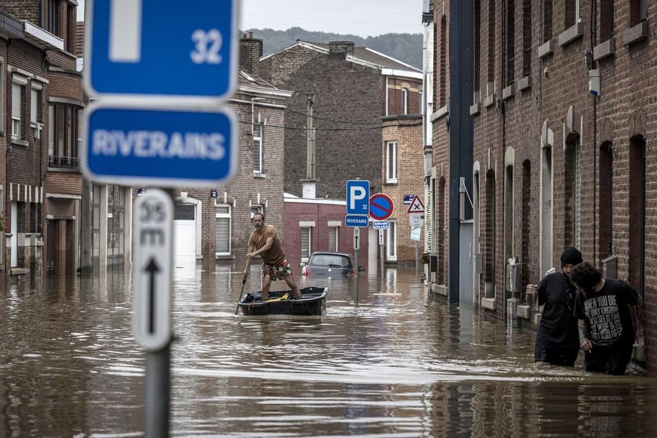 Belgien, Angleur: Ein Mann steuert ein Boot auf dem Hochwasser einer Straße nach heftigen Regenfällen. Schwere Überschwemmungen in Deutschland und Belgien haben Bäche und Straßen in reißende Ströme verwandelt, die Autos weggespült und Häuser zum Einsturz gebracht haben.