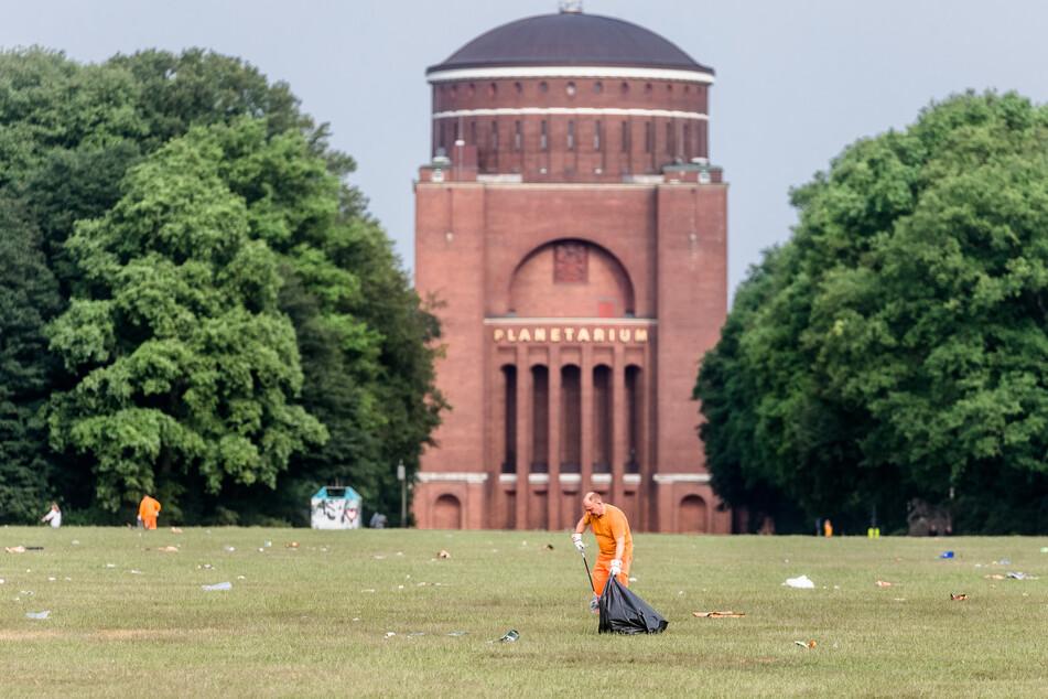 Ein Mitarbeiter der Stadtreinigung entfernt am frühen Morgen den Müll im Stadtpark. Künftig soll ihn ein Reinigungsroboter unterstützen. (Archivbild)