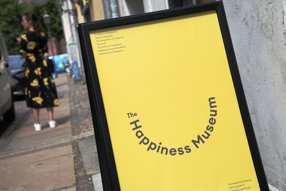 Eine Frau in einem geblümten Kleid steht vor dem Happiness Museum in Kopenhagen.