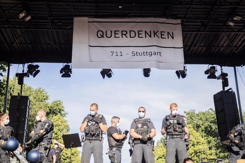 """Polizisten stehen bei einer Kundgebung gegen die Corona-Beschränkungen auf der Straße des 17. Juni auf der Bühne unter dem Banner der Initiative """"Querdenken 711""""."""