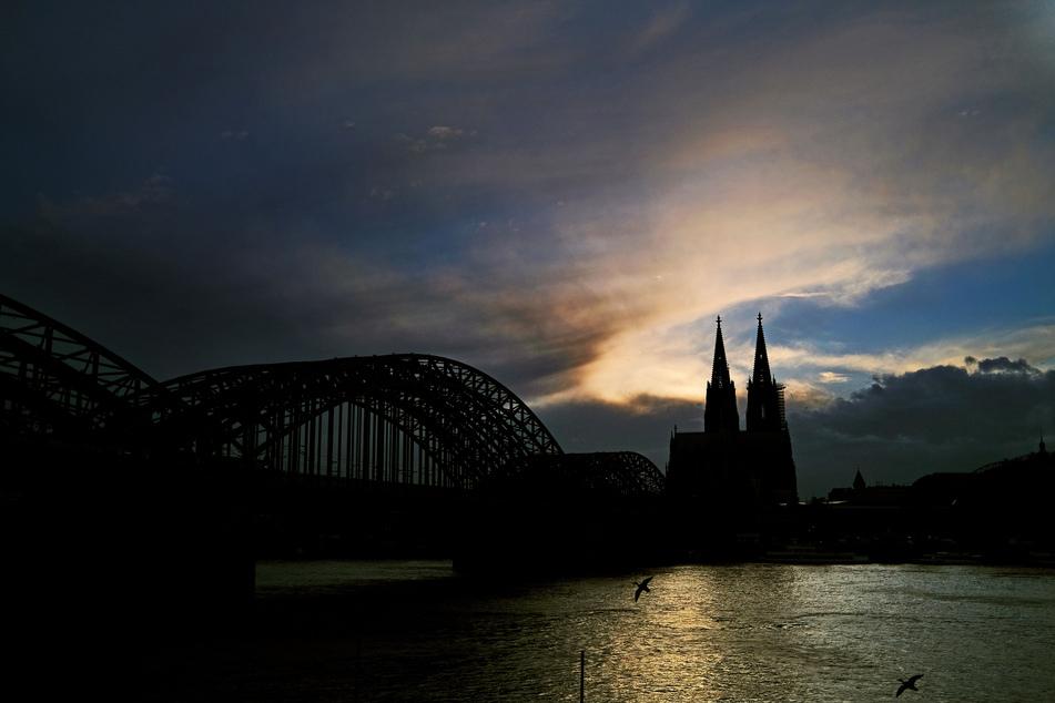 Hinter dem Dom ziehen Wolken an der Sonne vorbei. In NRW müssen sich die Menschen zum Start in die Osterferien am Wochenende auf unbeständiges Aprilwetter einstellen.