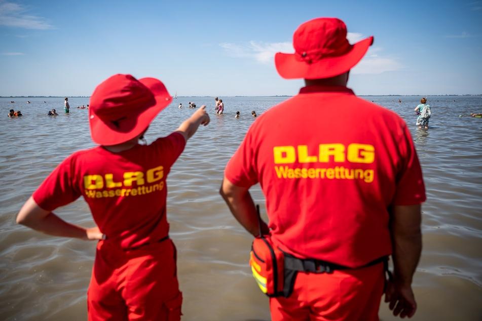 Mitglieder der DLRG (Deutsche-Lebens-Rettungs-Gesellschaft) stehen am Strand.
