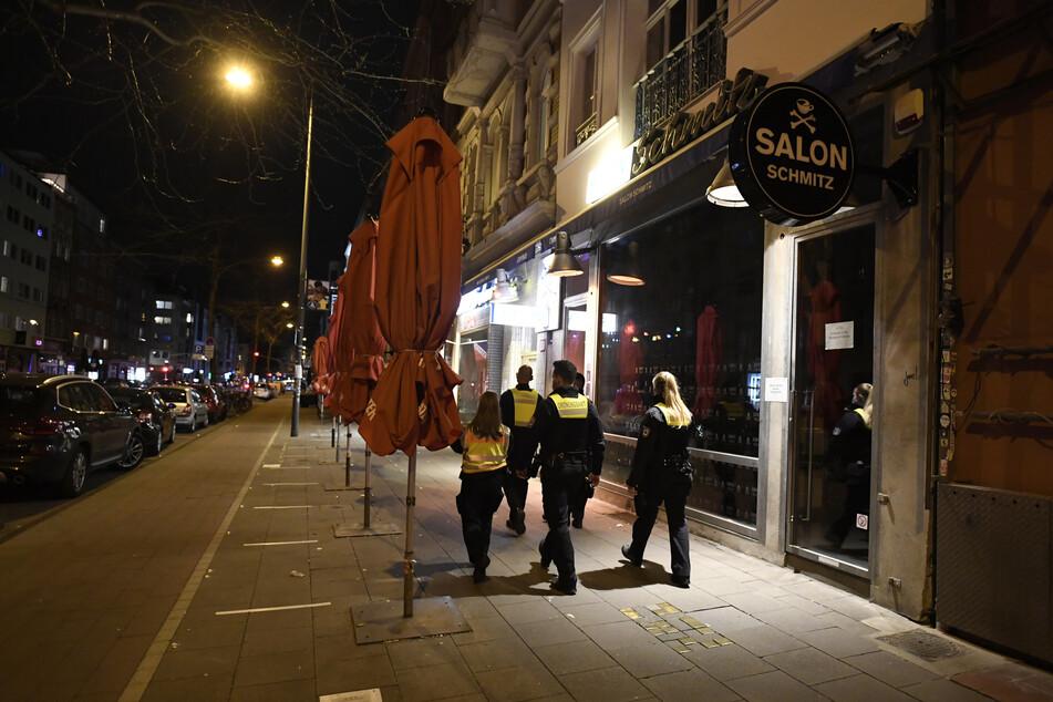 Das Kölner Ordnungsamt patrouilliert durch die verlassene Aachener Straße, wo sonst das Nachtleben tobt. Die Notbremse sieht unter anderem Ausgangsbeschränkungen von 22 Uhr bis 5 Uhr vor.