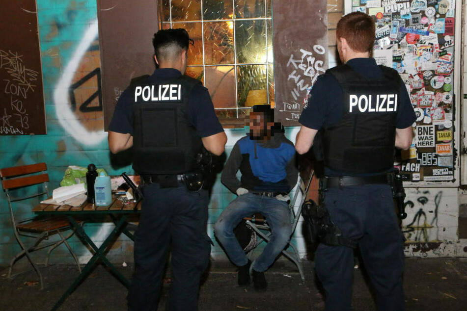 Polizisten bewachen den mutmaßlichen Brandstifter, der gefesselt auf einem Stuhl sitzt.