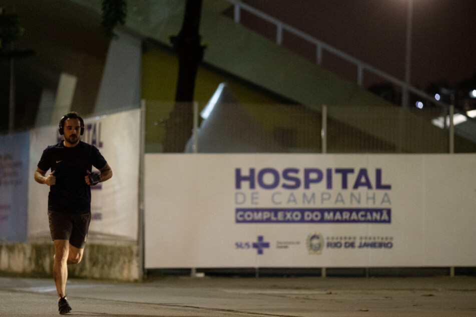 """Rio De Janeiro: Ein Mann läuft an einem Schriftzug vorbei """"Hospital de Campanha Complexo Do Maracana"""", vor dem Maracanã-Stadion, in dessen Anbau sich das Feldlazarett zur Behandlung von COVID19-Patienten befindet."""