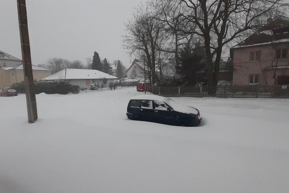 In Leipzig-Holzhausen verschwindet ein Auto im dichten Schnee.