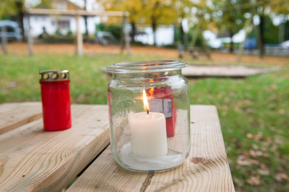 Kerzen stehen auf einem Kinderspielplatz, auf dem der Tote gefunden wurde, auf einem Tisch.