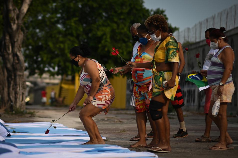 Demonstranten der NGO Rio de Paz halten neben Bahren mit Laken und Kissen Rosen hoch, während eines Protestes im Gedenken an die rund 300.000 Corona-Toten in Brasilien.