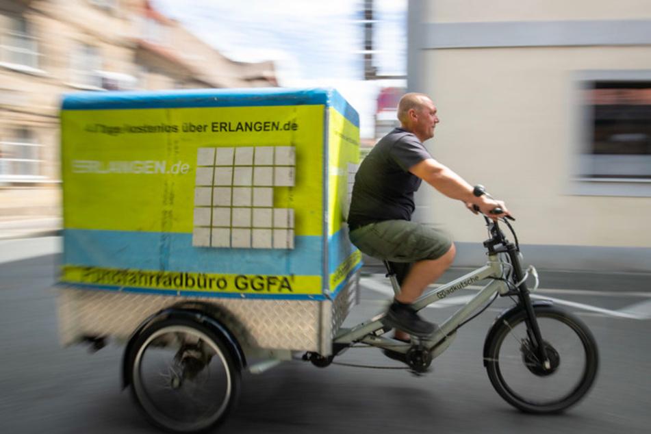 Andreas Reisch vom Cafe Hergricht, ein Verleih für Transporträder, fährt auf einem E-Lastenrad auf der Straße.